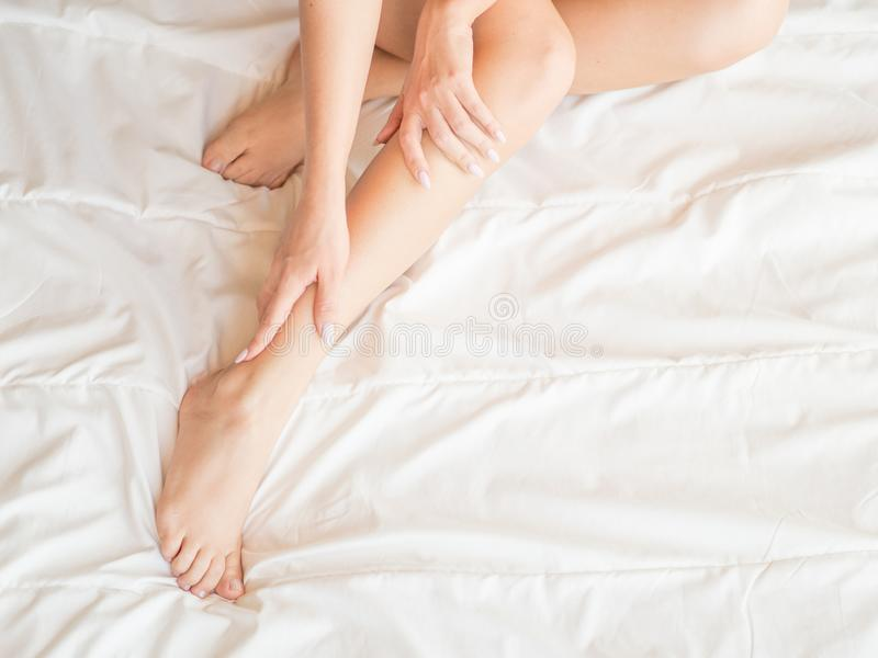 Closeup of pregnant woman hands doing foot massage royalty free stock photography