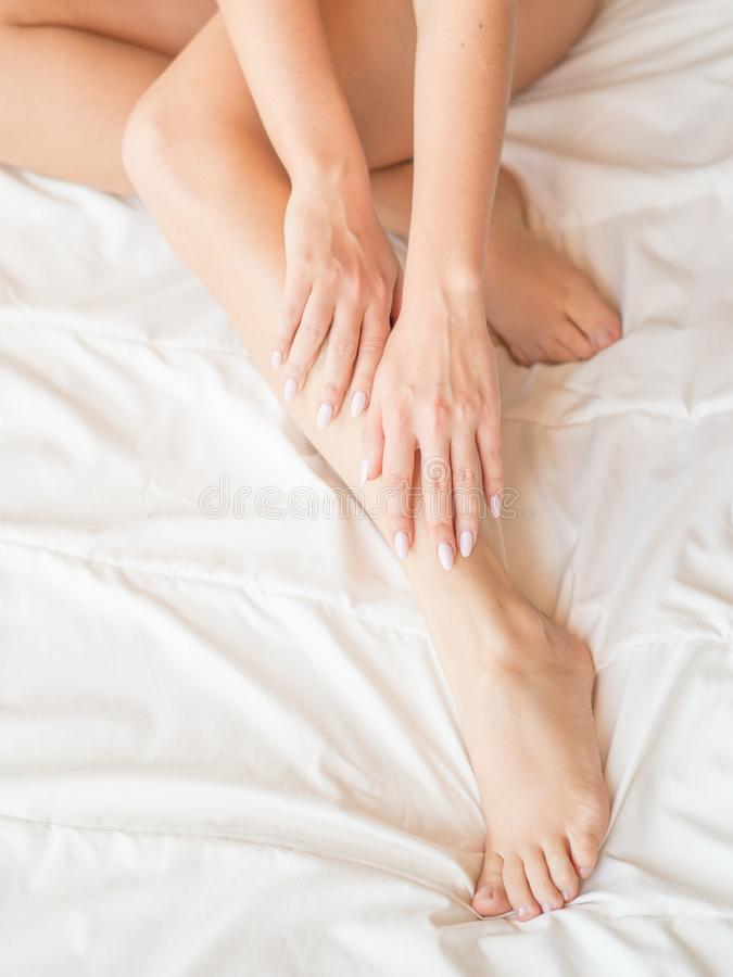 Closeup of pregnant woman hands doing foot massage royalty free stock photo
