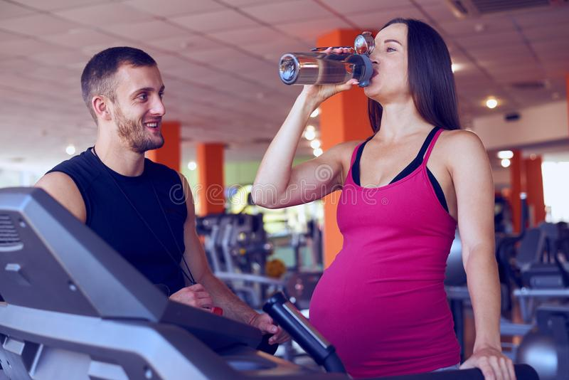 Pregnant woman drinking water while running on treadmill stock image