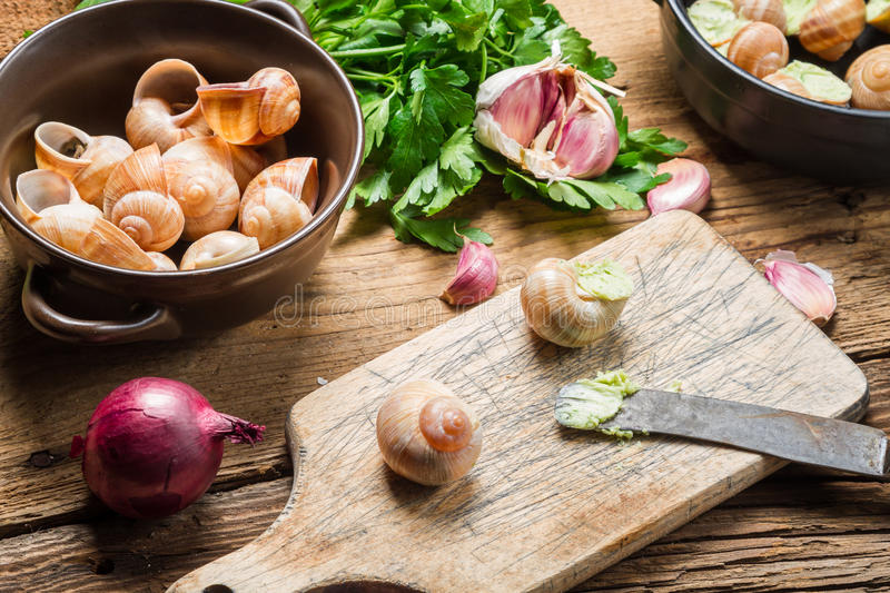 Closeup of preparing snails with garlic butter and herbs stock photos