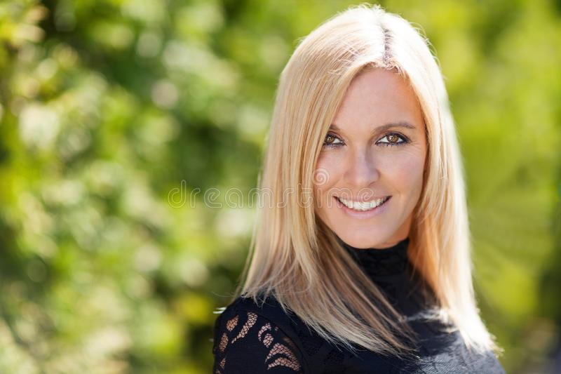 Closeup of a pretty blond smiling at the camera. She is outside on a trees background royalty free stock photos