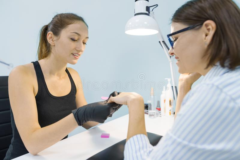 Closeup process of professional manicure. Manicurist woman hands in black gloves making manicure using professional tools. Nail. Closeup process of professional stock images