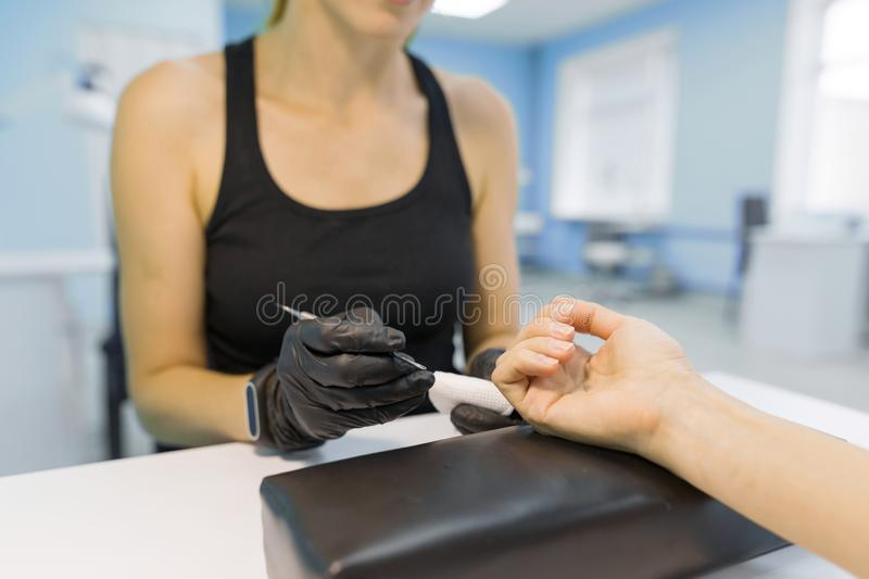 Closeup process of professional manicure. Manicurist woman hands in black gloves making manicure using professional tools. Nail. And hand care in beauty salon royalty free stock photography