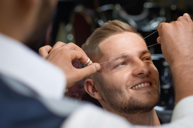 Closeup of process of threading procedure in barber shop. Professional barber correcting shape of brows with threads to smiling young men sitting in chair stock photo