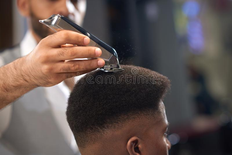 Closeup of process of trimming of hair in barber shop. Qualified barber keeping clipper in hands and correcting shape of hair to male client sitting on chair royalty free stock photos