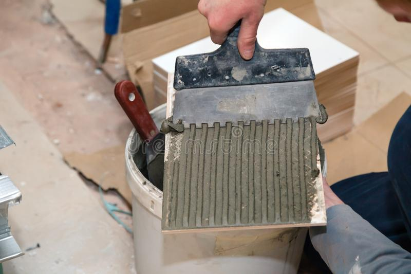 Closeup professional builder's hand smears cement glue on the ceramic tile with trowel to glue in bathroom. Concept renovation stock image