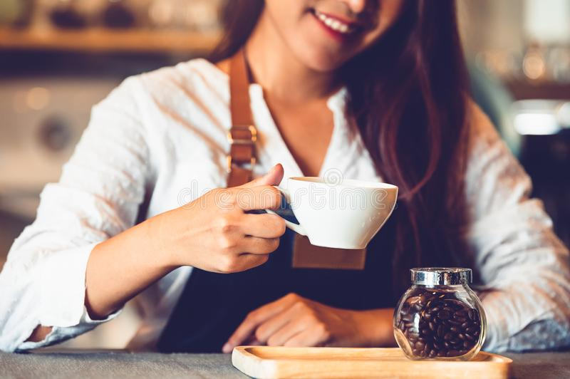Closeup of professional female barista hand making and holding white cup of coffee. Happy young woman at counter bar in restaurant royalty free stock images