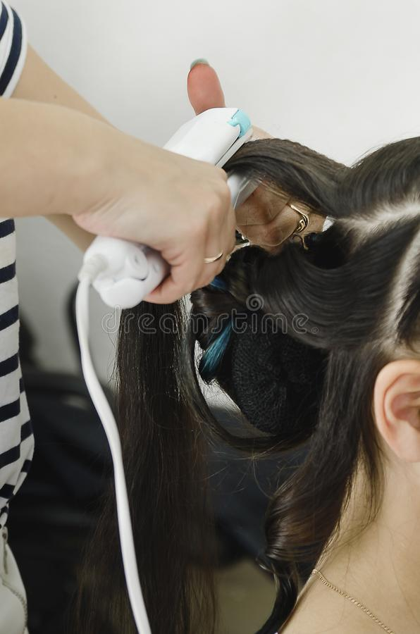 Closeup of a professional hairdresser`s hands doing a hairstyle in a beauty salon royalty free stock photo