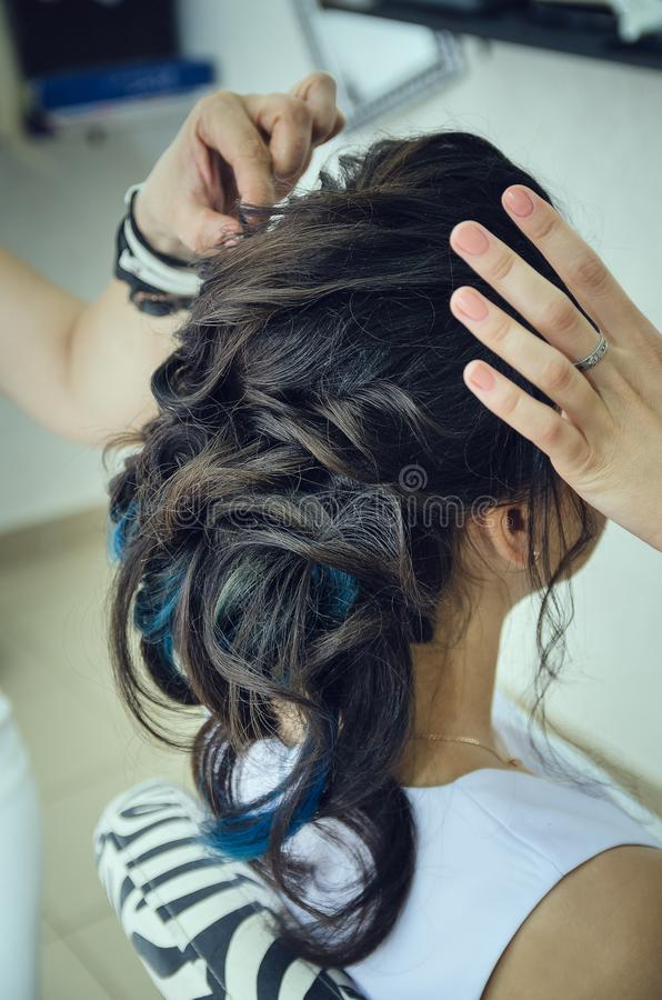 Closeup of a professional hairdresser`s hands doing a hairstyle in a beauty salon. Model of a brunette with long hair. The conc stock photo