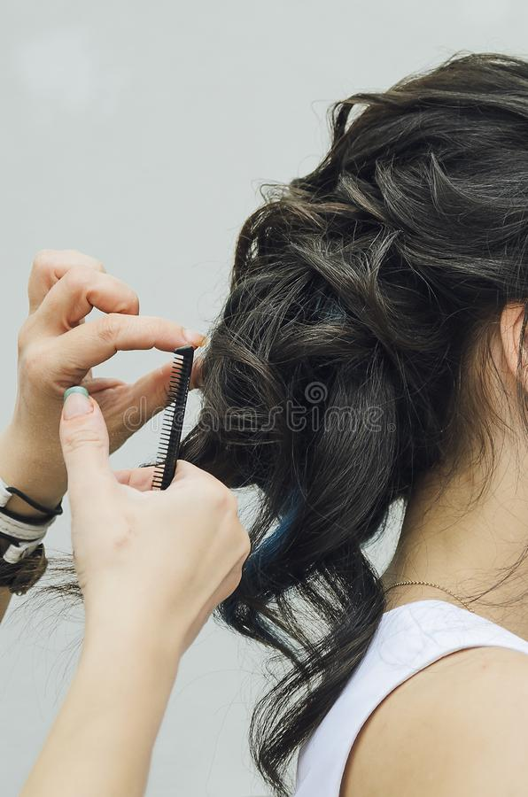 Closeup of a professional hairdresser`s hands doing a hairstyle in a beauty salon. Model of a brunette with long hair. The concep stock photography