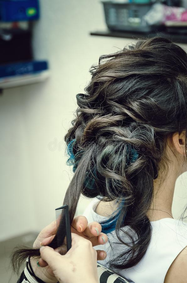 Closeup of a professional hairdresser`s hands doing a hairstyle in a beauty salon. Model of a brunette with long hair. The concep royalty free stock photo