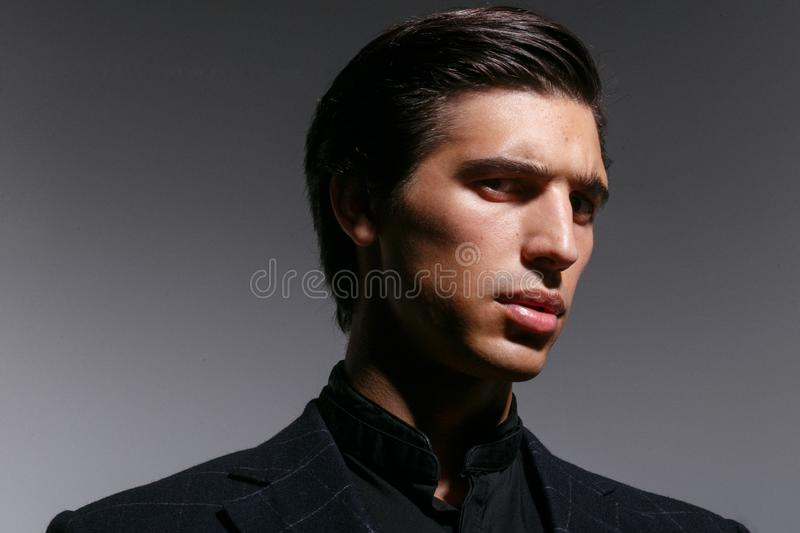 Closeup profile portrait of young man, isolated on a grey background, looking frowning a side. Horizontal indoors shot. stock photo