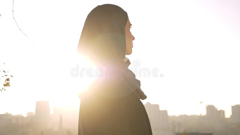 Closeup profile shoot of young attractive female silhouette in hijab looking forward being turned to the side with urban stock images