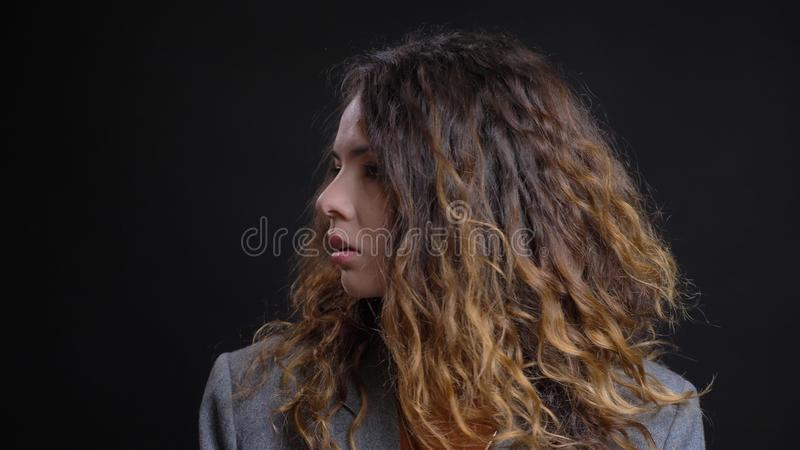 Closeup profile shoot of young pretty caucasian female with brunette curly hair looking forward with background isolated royalty free stock photography