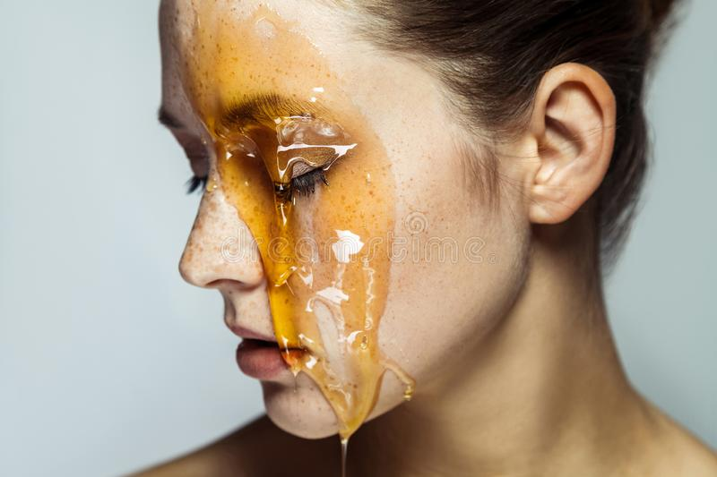 Closeup profile side view portrait of beautiful young brunette woman with freckles and honey on face with closed eyes and serious royalty free stock photo