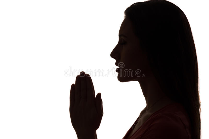 Closeup profile of a woman praying in silhouette isolated royalty free stock image
