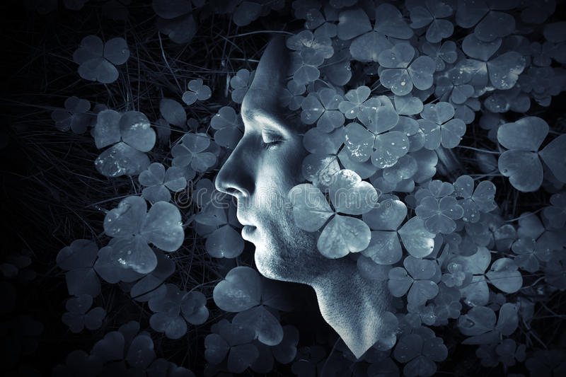 Closeup profMale profile and dark blue wild Oxalis grass forest backgroundile portrait of young Caucasian man with closed eyes stock images