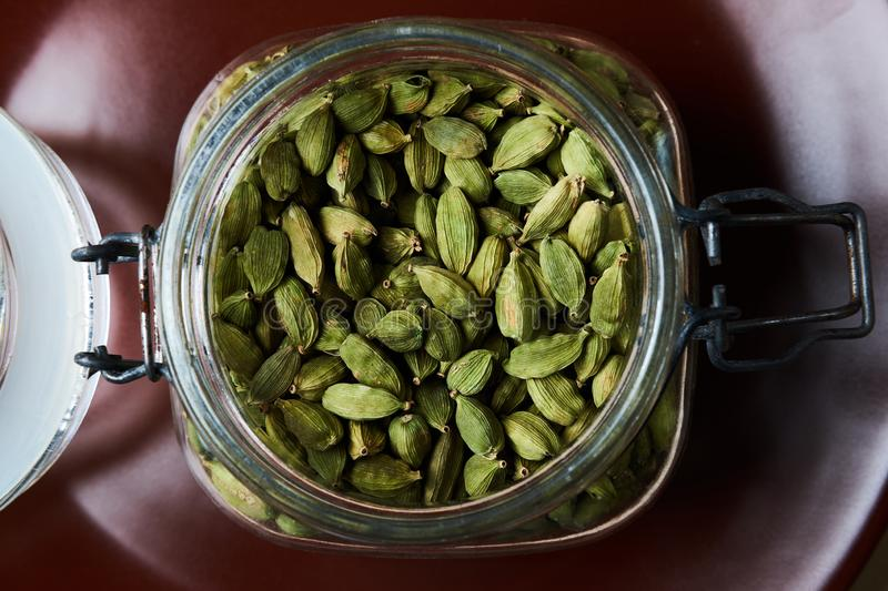 Closeup proto of glass jar full of green cardamom pods on brown plate royalty free stock photos