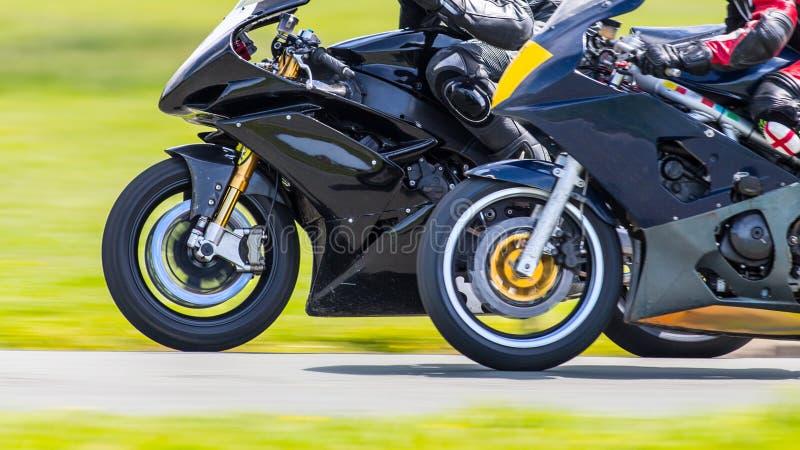 Closeup racing motorbikes. Closeup of racing motorbikes passing on track royalty free stock image