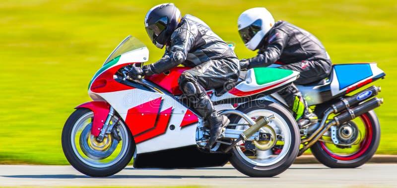 Closeup racing motorbikes. Closeup of racing motorbikes passing on track royalty free stock photography