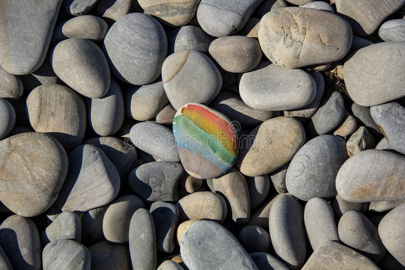 Closeup of rainbow painting on stone pebble on pebble sea beach. In summer, coast, background, color, acrylic, activity, art, artistic, backdrop, pattern royalty free stock photography