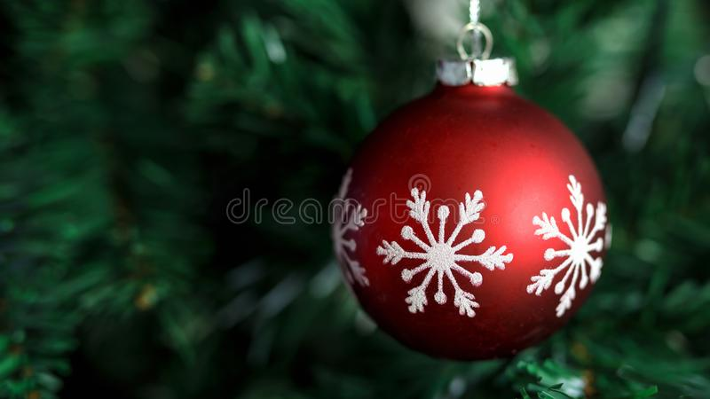 Closeup of red bauble hanging on decorated Christmas and New Year tree stock photos