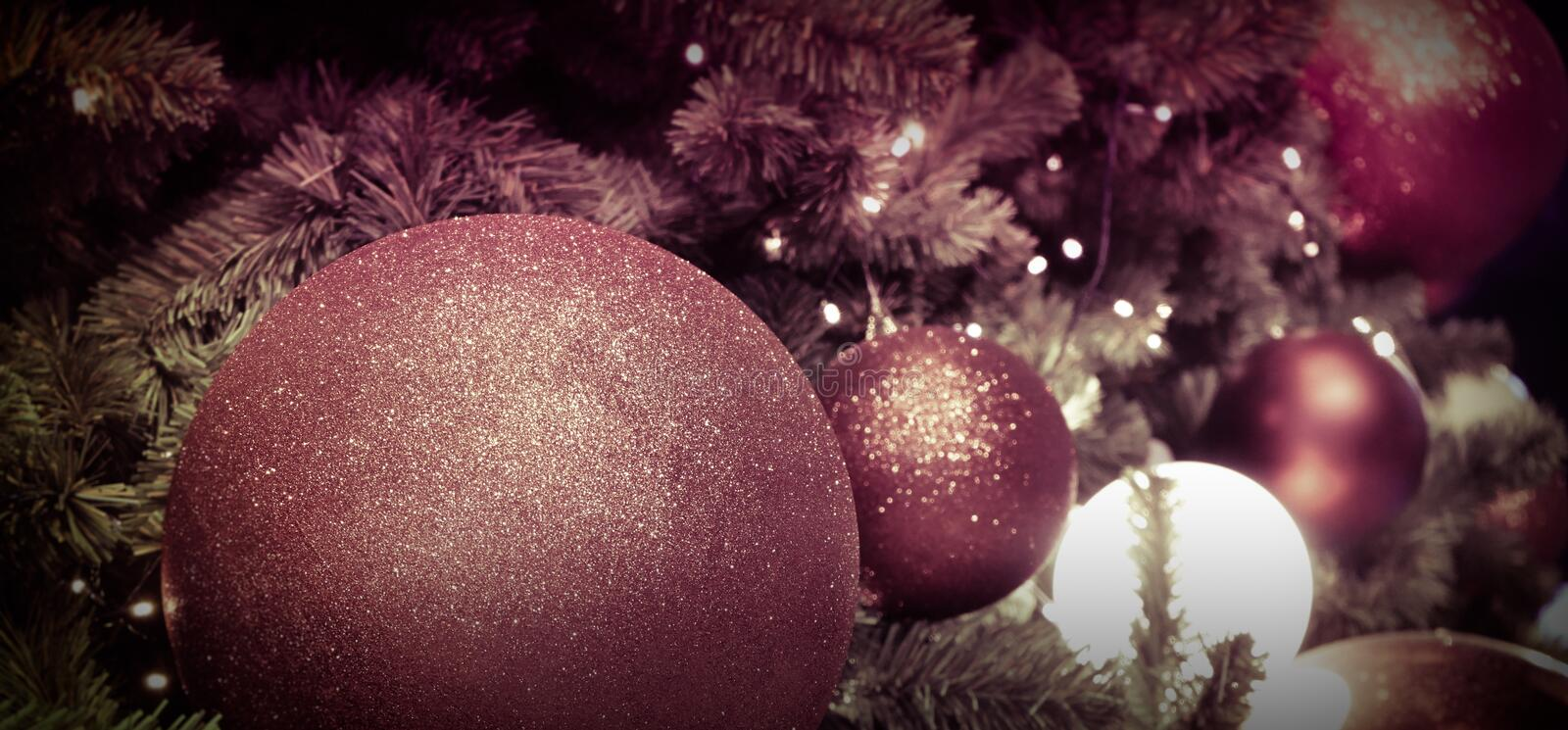 Closeup of red and colorful bauble hanging from a decorated Christmas tree royalty free stock images