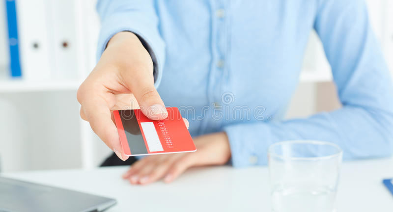 Closeup of red credit card holded by hand. Focus on hand stock photos