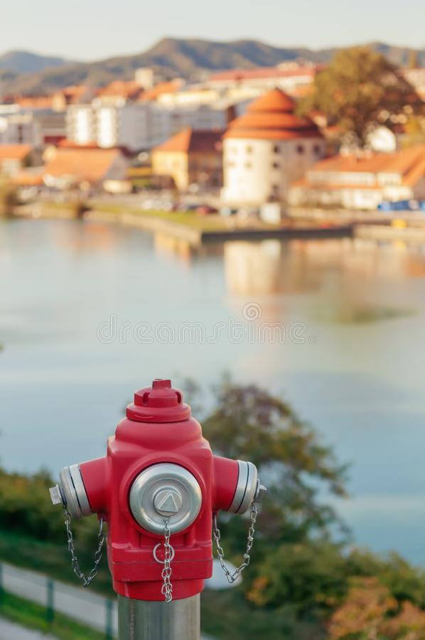 Closeup of red fire hydrant and sunlit old town by the river in background. Fire safety, fire extinguishing, accidents and urbanism concepts royalty free stock photos