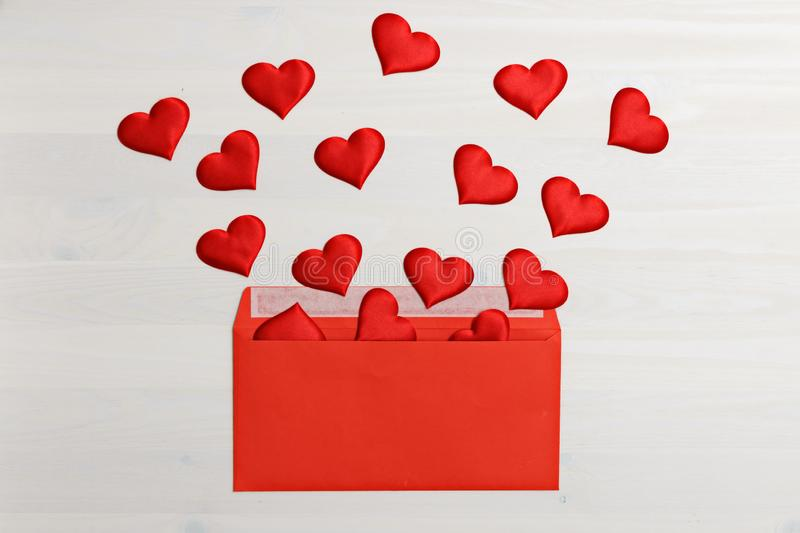 Closeup of red hearts flying out of a red paper envelope on a white wooden background. Valentines day celebration concept stock image