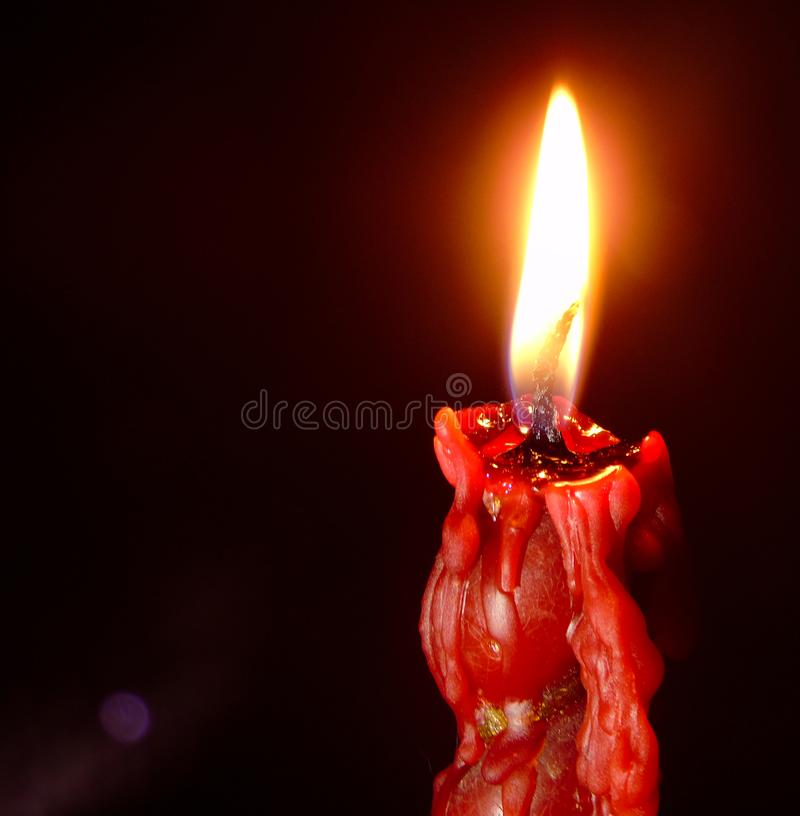 Closeup of red lit candle isolated on dark red background, fire, flame. Closeup of red lit candle, hot fire, wax, beeswax. Burning red candle on black background royalty free stock images