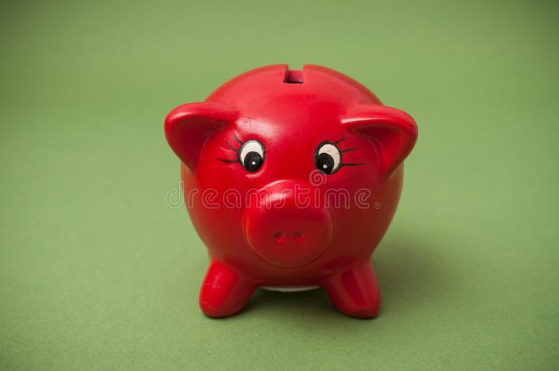 Red piggy bank on green background. Closeup of red piggy bank on green background royalty free stock images