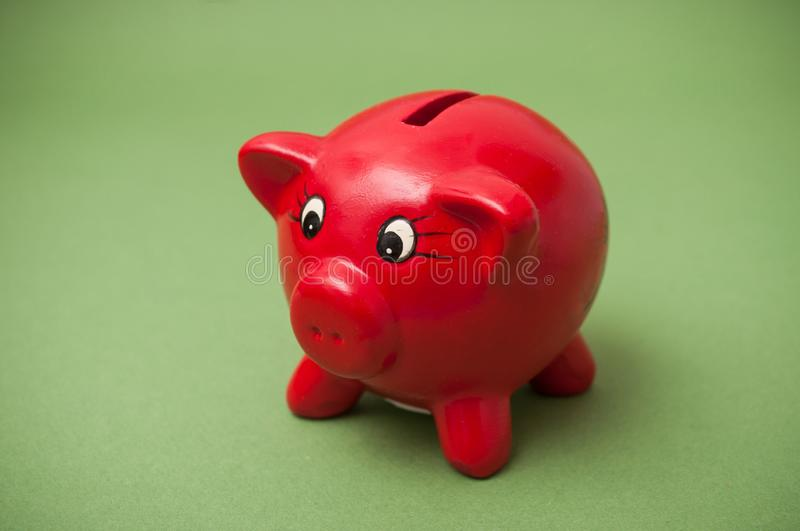 Red piggy bank on green background. Closeup of red piggy bank on green background royalty free stock photo