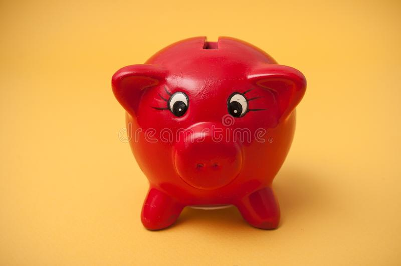 Red piggy bank on yellow background. Closeup of red piggy bank on yellow background stock photography