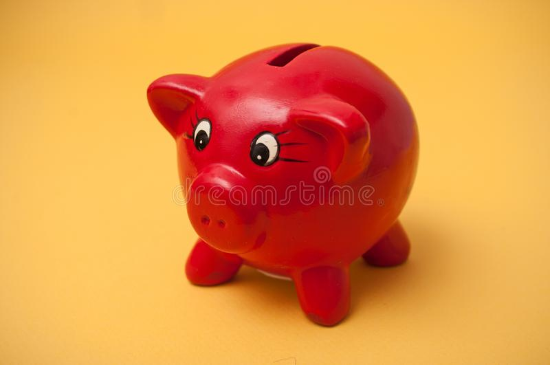Red piggy bank on yellow background. Closeup of red piggy bank on yellow background stock photo