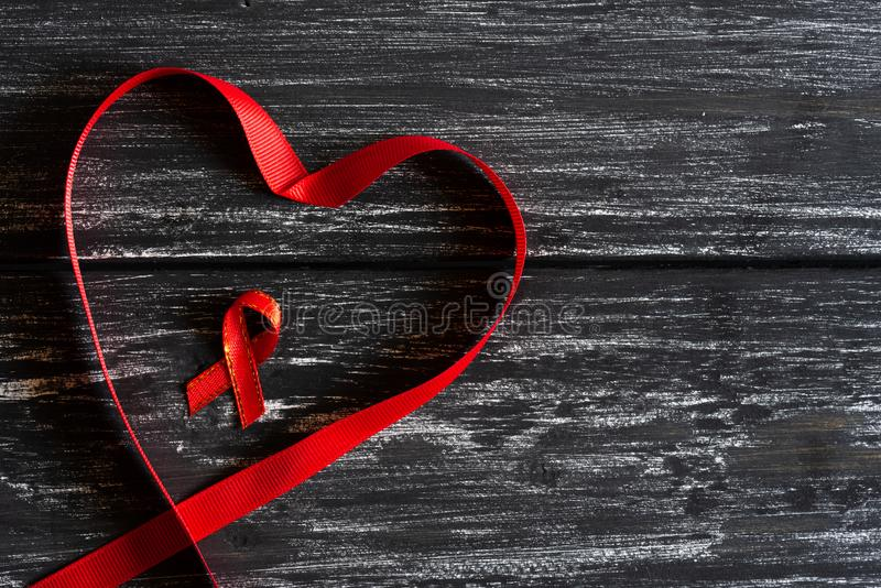 Closeup red ribbon in shape of heart awareness. On black wooden table background for World Aids day campaign royalty free stock photos
