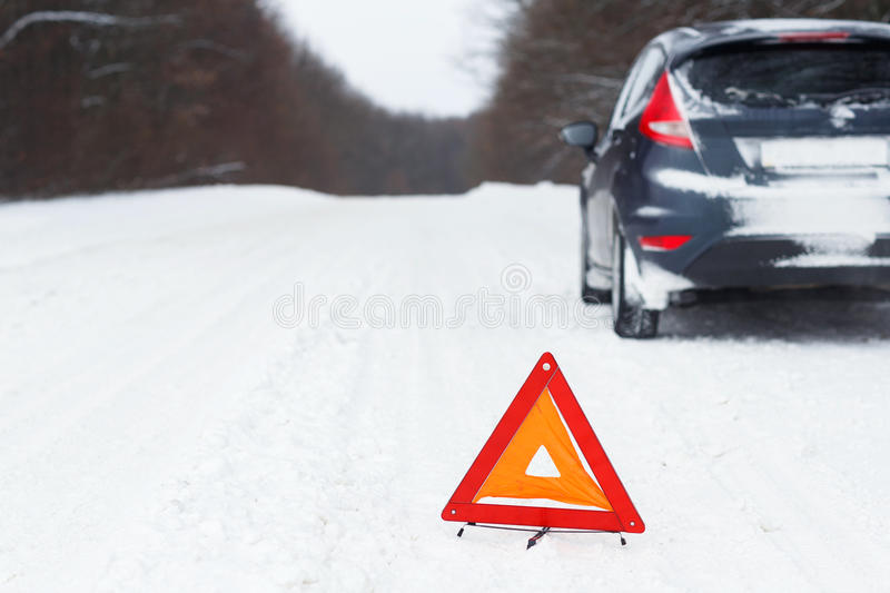 Closeup of red warning triangle with a broken down car royalty free stock image