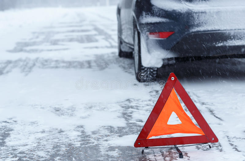 Closeup of red warning triangle with a broken down car in winter royalty free stock images