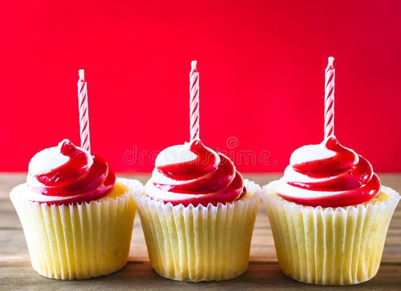 Red and white cupcakes with candles on wood background stock photos