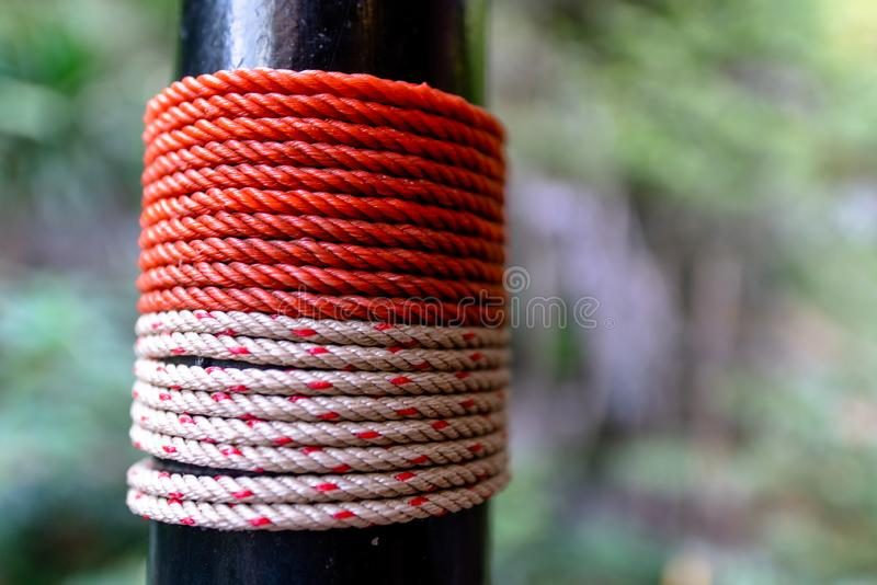 Closeup of red and white nylon rope tied to black pole. Closeup of red and white nylon rope tied to black pole with blurred green background royalty free stock photo