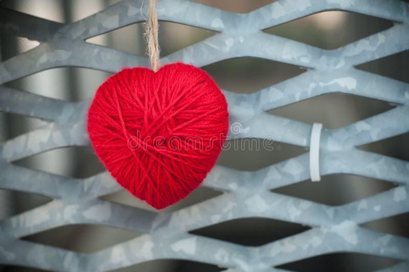 Red woolen heart in outdoor on metallic grid stock image