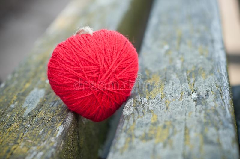 Red woolen heart in outdoor on wooden bench royalty free stock photography