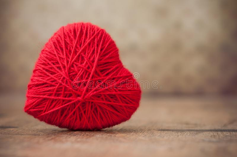 red woolen heart on wooden table background stock image