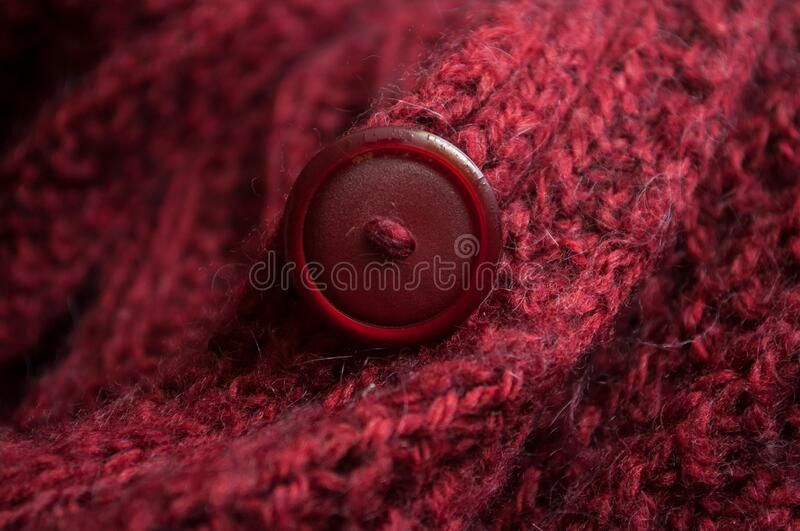 Red woolen pullover texture with plastic button. Closeup of red woolen pullover texture with plastic button royalty free stock image