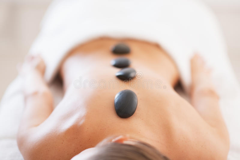 Closeup on relaxed young woman receiving hot stone massage stock photos