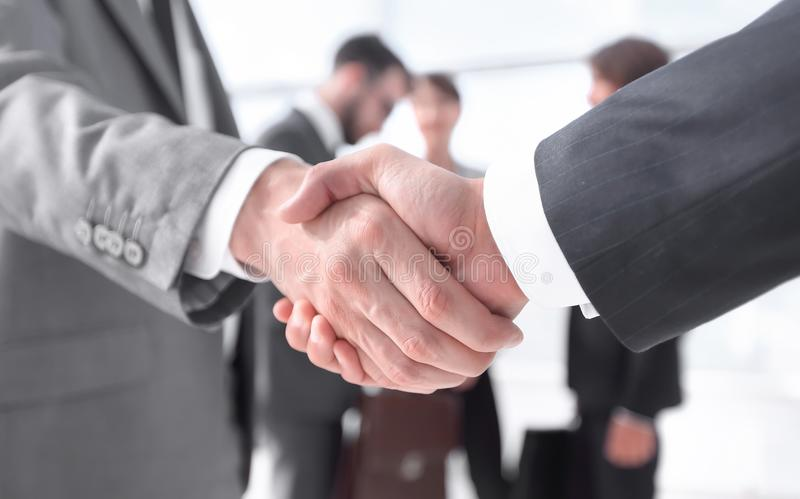 Closeup.reliable handshake of business partners. On the background of business team stock photo