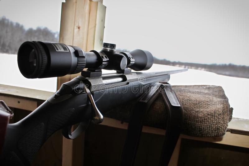 Closeup of a rifle bolt and scope while hunting.  stock image