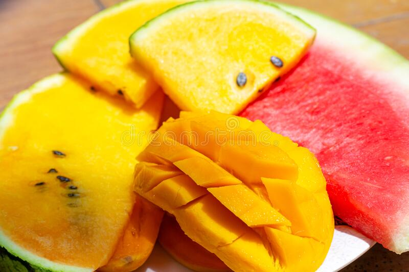 Closeup ripe juicy sliced fruits of mango and red and yellow watermelon. Sweet and colorful fruit plate.  stock photos