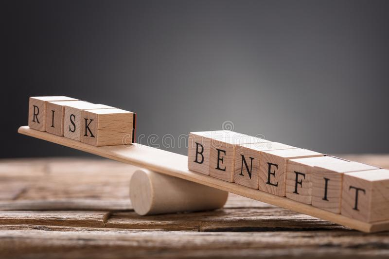 Closeup Of Risk And Benefit Wooden Blocks On Seesaw. Against gray background stock images