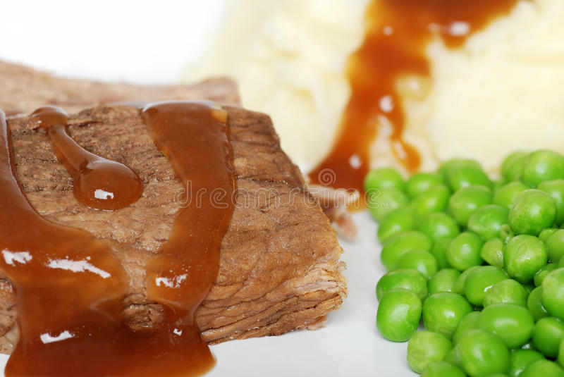 Closeup roast beef with gravy and vegetables stock photography